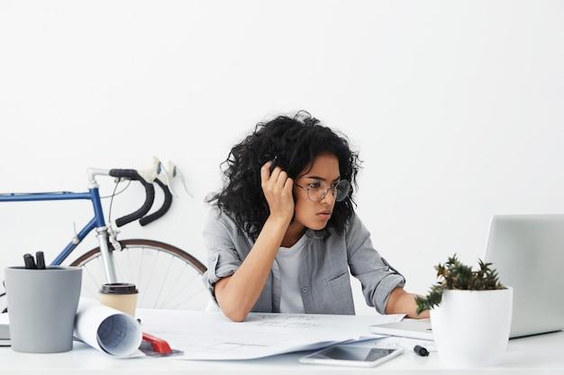 大きな眼鏡をかけている疲れたビジネス企業家の浅黒い肌の女性のショット