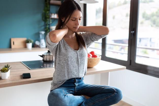 自宅のキッチンのスツールに座って首の痛みに苦しんでいる疲れた若い女性のショット。
