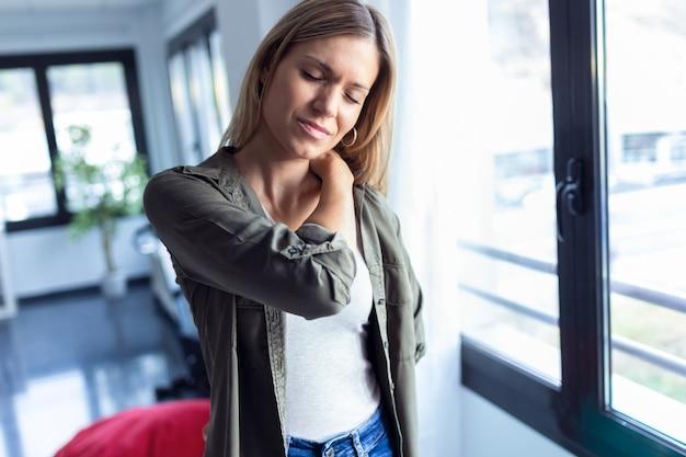Выстрел усталой молодой женщины с болью в шее и спине, стоящей в гостиной дома.