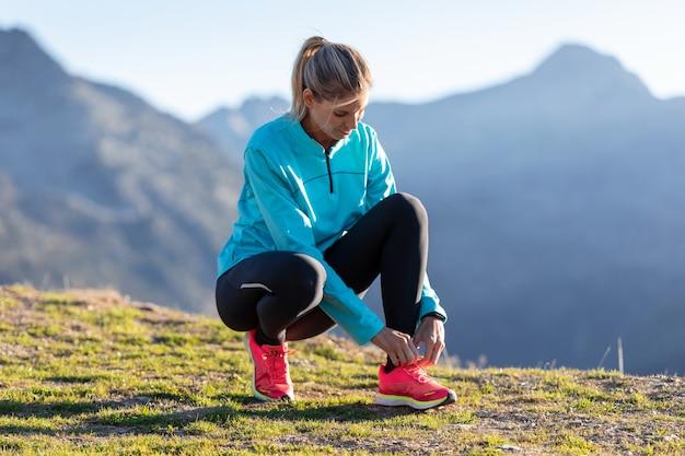 山でトレーニングを行う前に、ランニングシューズに靴ひもを結ぶトレイルランナーの女性のショット。