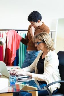 На снимке две красивые бизнес-леди сравнивают цвета текстильного онлайн-каталога с тканями в офисе.