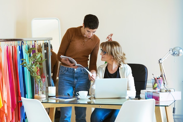 Снимок двух красивых деловых женщин, просматривающих каталог текстиля в ноутбуке в офисе.