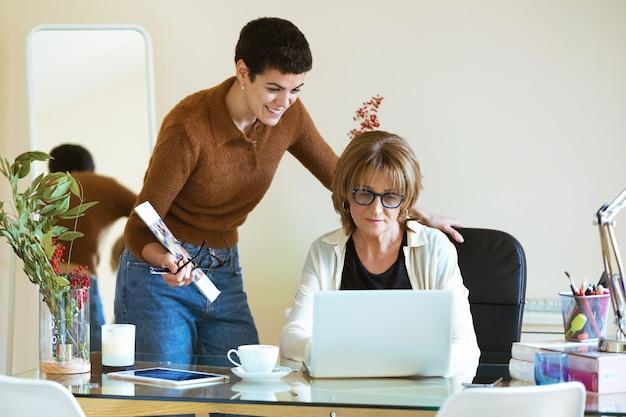 Выстрел из двух красивых деловых женщин, работающих вместе с ноутбуком в офисе.