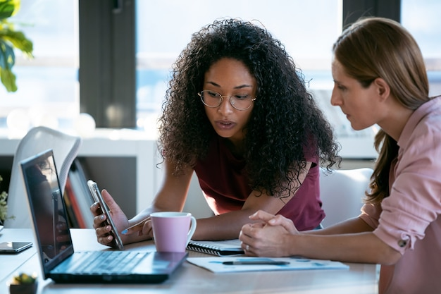 Выстрел из двух красивых деловых женщин, работающих вместе с ноутбуком, обсуждая новости о работе в офисе.