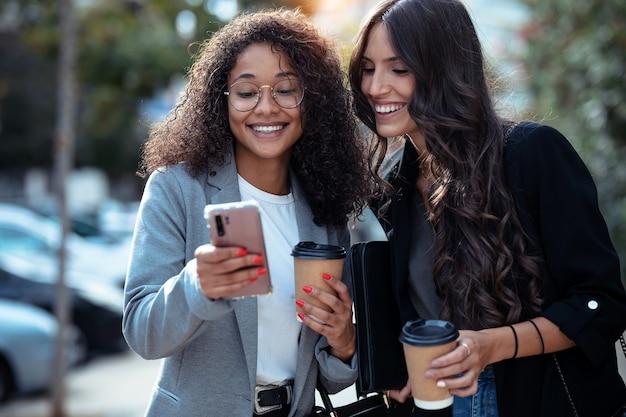 Выстрел из двух красивых женщин-предпринимателей, использующих смартфон во время прогулки по городу за чашкой кофе.