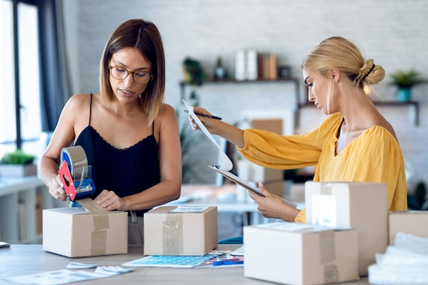 두 명의 아름다운 프리랜서 여성 판매자가 소규모 창업 고객에게 온라인으로 주문한 배달 제품을 위해 판지 상자를 포장하고 밀봉하면서 제품 주문을 확인하는 사진