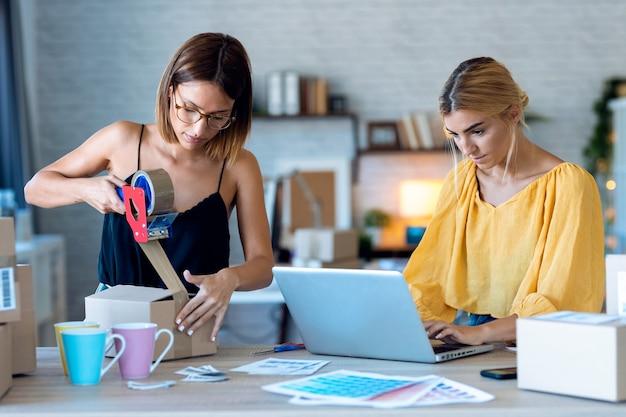 두 명의 아름다운 프리랜서 여성 판매자가 컴퓨터로 제품 주문을 확인하는 동안 고객에게 온라인으로 주문한 배달 제품을 위해 판지 상자를 포장하고 밀봉하는 사진