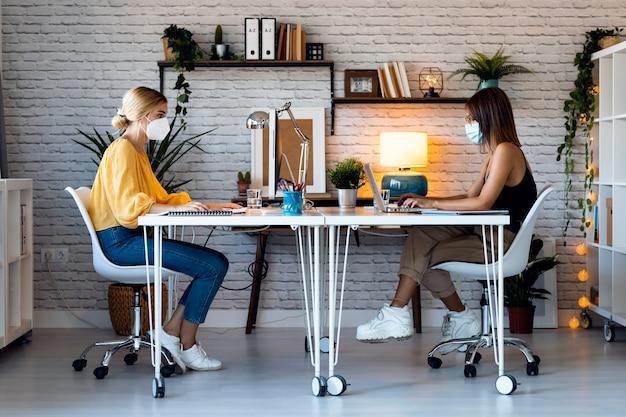スタートアップの中小企業でコンピューターを使用しているときに衛生的なフェイスマスクを身に着けている2人の美しいフリーランスのビジネス女性の売り手のショット。社会距離拡大の概念。