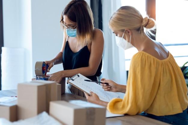 スタートアップの中小企業で段ボール箱を梱包して密封しながら製品の注文を確認しながら、衛生的な顔のマスクを身に着けている2人の美しいフリーランスのビジネス女性の売り手のショット。
