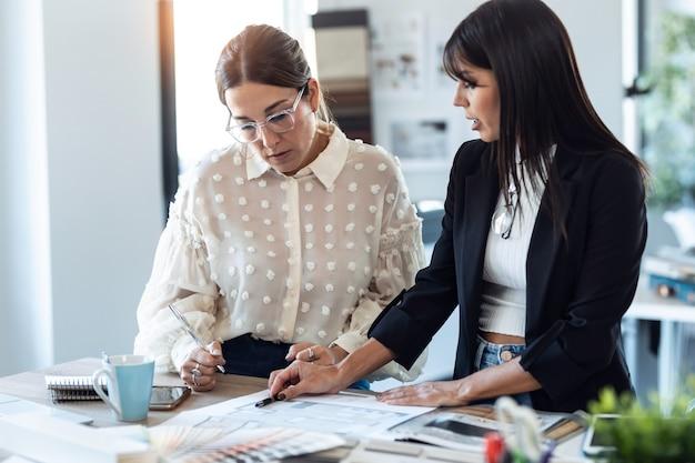 Снимок двух красивых молодых дизайнеров, работающих над дизайнерским проектом, выбирая материалы в офисе.