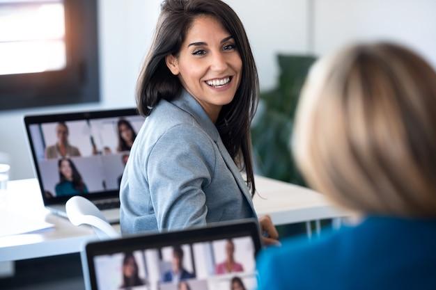 사무실에서 노트북으로 온라인 브리핑을 하면서 다양한 동료들과 화상 통화를 하는 동안 두 명의 비즈니스 여성이 말하는 장면.