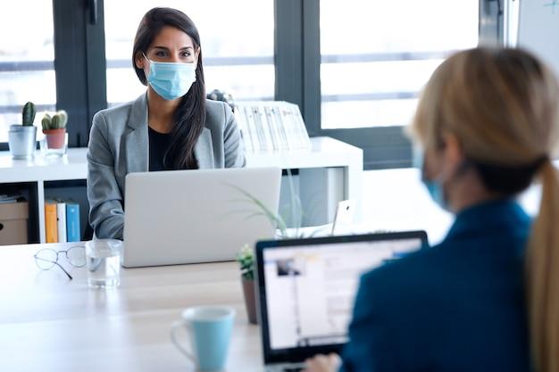 공동 작업 공간에서 노트북 작업을 하는 동안 위생적인 안면 마스크를 쓴 두 명의 비즈니스 여성의 사진. 사회적 거리 개념입니다.