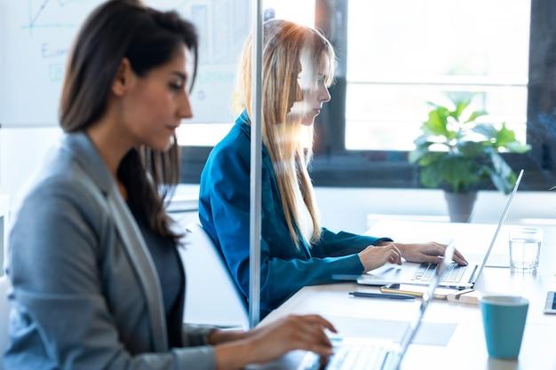 두 명의 비즈니스 여성이 공동 작업 공간의 분할된 책상에서 노트북으로 작업하는 모습을 촬영했습니다. 사회적 거리의 개념입니다.