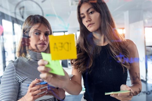 현대 스타트업 사무실에서 포스트잇 스티커를 붙이고 벽 유리에 함께 일하는 두 명의 젊은 여성의 사진.