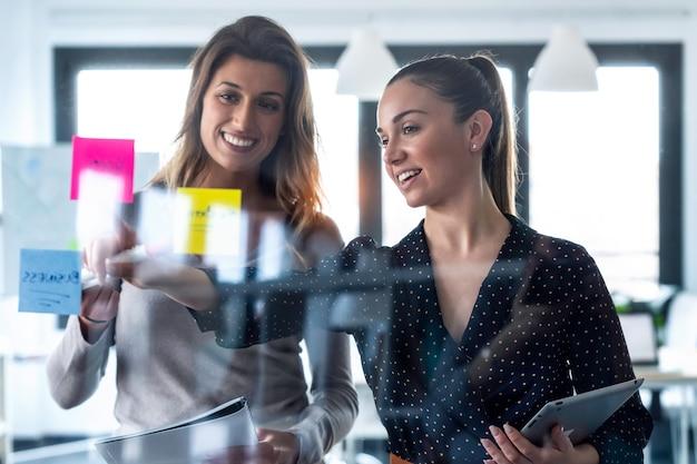 공동 작업 공간에 스티커를 붙이고 벽 유리에서 함께 일하는 두 명의 젊은 여성의 사진.