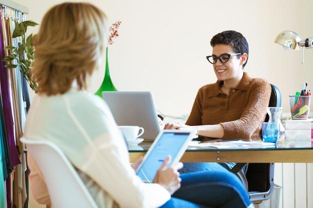 オフィスでラップトップとデジタルタブレットを使って仕事についてアイデアを交換する2人のビジネスウーマンのショット。