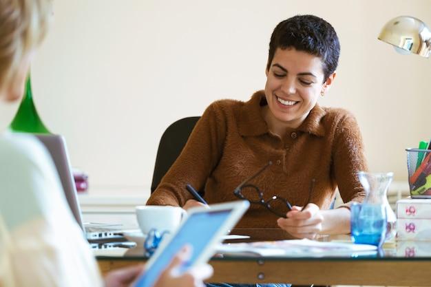 仕事について話し、オフィスでデジタルタブレットとアイデアを交換する2人のビジネスウーマンのショット。