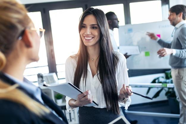 공동 작업 공간에서 일에 대해 이야기하는 두 명의 우아한 젊은 비즈니스 여성의 총.