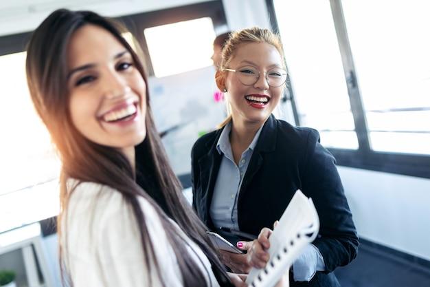 두 명의 우아한 젊은 여성 경제인이 미소를 지으며 공동 작업 공간에서 카메라를 바라보고 있는 사진입니다.