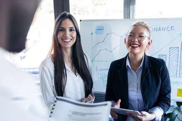 두 명의 우아한 젊은 여성 경제인이 코워킹 스페이스에서 회의를 하며 동료를 바라보며 웃고 있습니다.