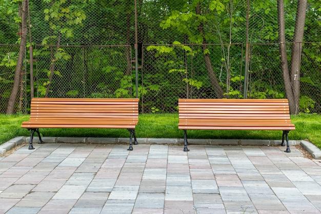 新鮮な緑の草に囲まれた公園で2つの無料のベンチのショット