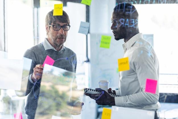 Выстрел из двух красивых деловых людей, пишущих заметки на стеклянной доске офиса во время совместного обсуждения в коворкинге.