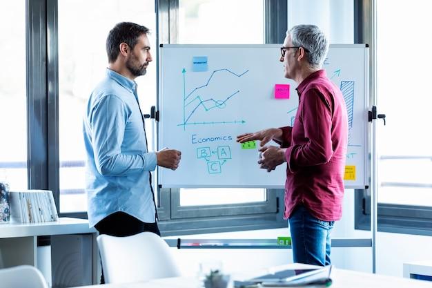 コワーキングスペースでホワイトボードのデータを操作している2人のハンサムなビジネスマンのショット。