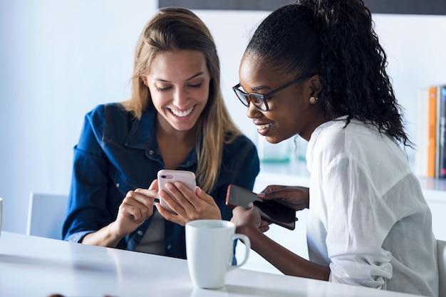 オフィスで休憩中に携帯電話を一緒に使用している2人のかなり若いビジネスウーマンのショット。