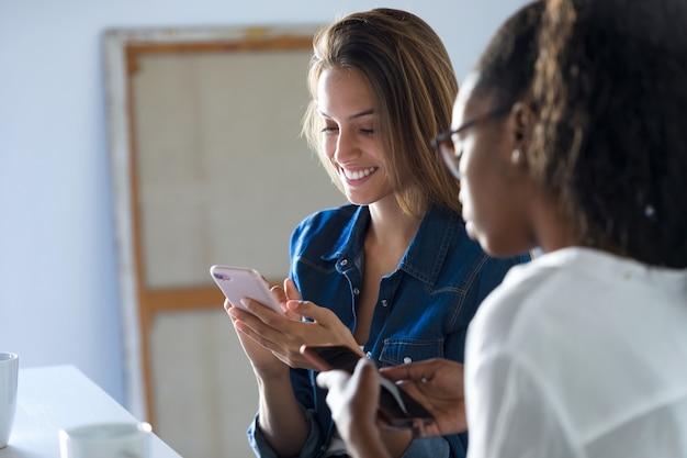 オフィスで携帯電話を使用している2人のかなり若いビジネスウーマンのショット。