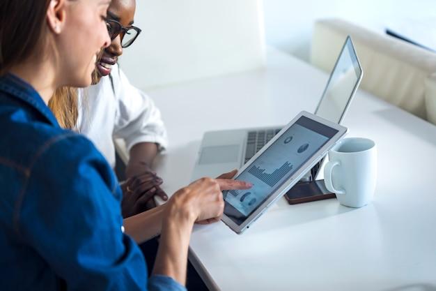 オフィスでデジタルタブレットと一緒に働いている2人のかなり若いビジネスウーマンのショット。