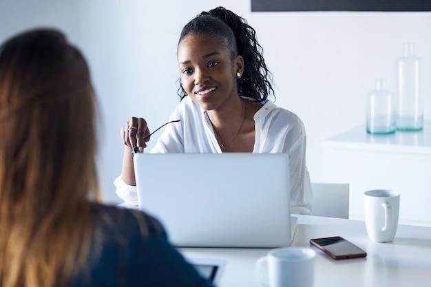 オフィスでデジタルタブレットとラップトップを使用して作業している2人のかなり若いビジネスウーマンのショット。
