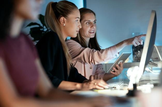 オフィスで話している間、コンピューターとデジタルタブレットで一緒に働いている2人の賢いビジネスウーマンのショット。