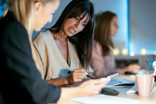 Выстрел из двух умных деловых женщин, работающих вместе с цифровым планшетом во время разговора в офисе.