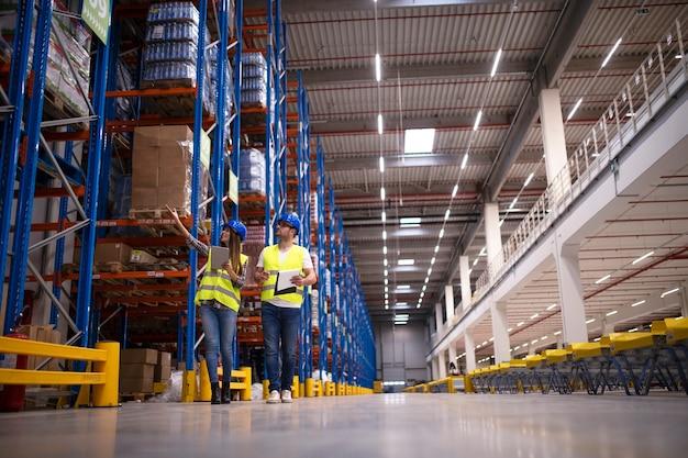 대형 창고 센터를 걷고있는 두 명의 작업자가 상품이있는 선반을 관찰하고 시장에 유통을 계획하는 장면
