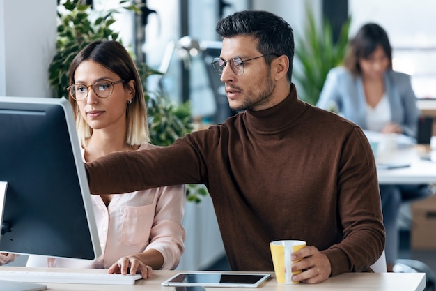 현대 작업 공간에서 컴퓨터 디지털 태블릿과 함께 일하는 두 젊은 비즈니스 동료의 사진. 브레인스토밍 개념입니다.