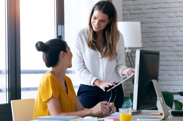2人の若いビジネスウーマンが、オフィスのデジタルタブレットで最後に働いていることを話したりレビューしたりするショット。