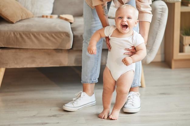 Снимок неузнаваемой женщины в джинсах, помогающей своему веселому маленькому ребенку учиться ходить