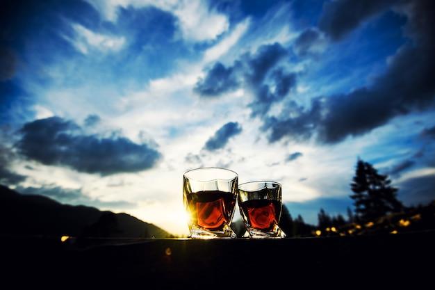 山の風景の背景に夕日の劇的な空でウイスキーのショット