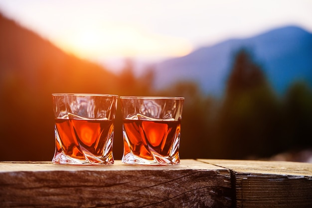 山の風景の表面の日没の劇的な空でウイスキーのショット