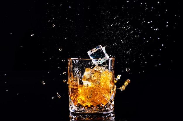 黒い表面にスプラッシュ、グラスのブランデーとウイスキーのショット