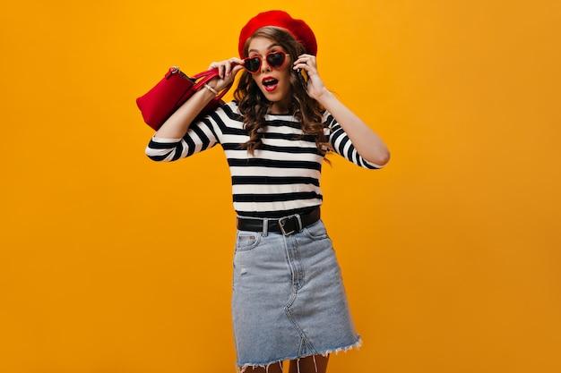 Выстрел женщины в красном берете, снимающей солнцезащитные очки и разговаривающей по телефону. современная девушка с волнистыми волосами в полосатой блузке с сумочкой позирует.