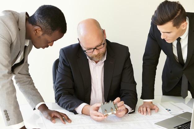 Снимок рабочего процесса в конструкторском бюро. трое мужчин в офисной одежде рассматривают новый перспективный проект. главный инженер-конструктор сидит за столом, рядом стоят его сослуживцы.