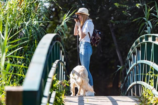 Снимок молодой женщины-любителя фотографировать пейзаж во время прогулки со своей собакой, пересекающей мост в парке.