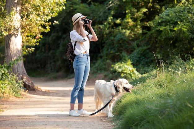 Выстрел молодой женщины любительской фотографии фотографируя пейзаж во время прогулки со своей собакой в парке.