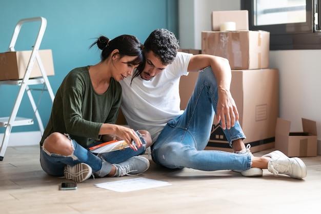 바닥에 앉아 있는 동안 아파트 벽을 칠하기 위해 색상 팔레트에서 색상을 선택하는 젊은 매력적인 커플의 샷.
