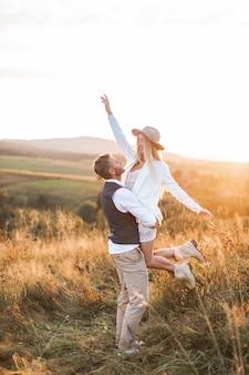 夏の畑でハンサムなボーイフレンドによって運ばれている自由奔放に生きる若いヒッピー女性のショット