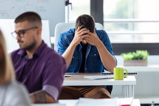 Выстрел молодого бизнесмена, держащего лицо руками, сидя за столом в творческом офисе. напряженный день в офисе.