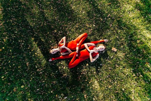 Выстрел молодой пары, занимающейся акробатической йогой на лужайке.