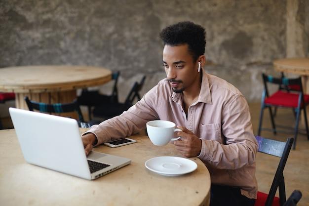 젊은 어두운 피부의 남성 프리랜서의 총은 현대 노트북과 스마트 폰이있는 커피 하우스에서 원격으로 작업하는 베이지 색 셔츠를 입고 집중된 얼굴로 화면을보고 커피 한잔 들고