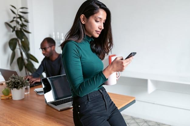 オフィスで携帯電話でメッセージを送信する若いインドのビジネスウーマン起業家のショット。